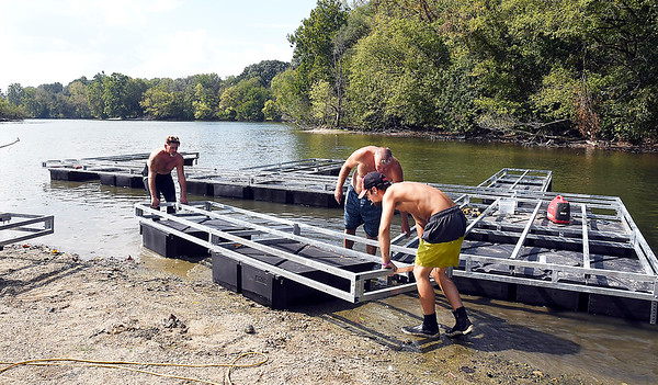 John P. Cleary | The Herald Bulletin<br /> Workers from LakeMaster Inc. of Muncie move another section into place as they assemble new boat docks in the shallow waters of the south lake at Shadyside Park Monday. The new docks will replace the old ones located at the bait shop.