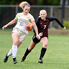 Blake Newman, of Defiance, and Anderson University's Katie Essick go after the ball to gain possession.