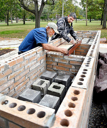 Randy Davis and Jeffery Gibson, of RD Masonry, work on this brick structure Friday that will house an historic bell and display at the Centennial Prayer Labyrinth on the Anderson University campus. The bricks being used for the project came from an old college building that were saved to be reused.
