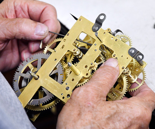 The hands of clockmaker Joe Remington as he works on this clock mechanism.