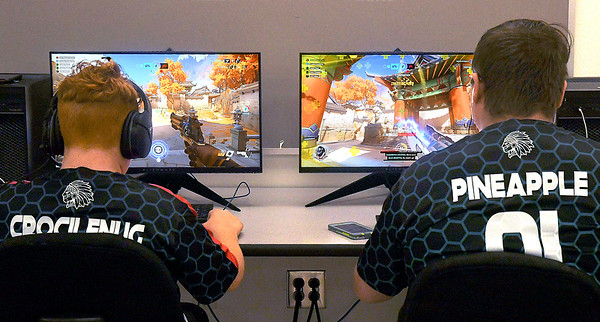 Anderson High School E-Sports Club members Braden Flatford and Noah Heffelmire, with their gamer name on the back of their shirts, run through the video game as they practice after school.