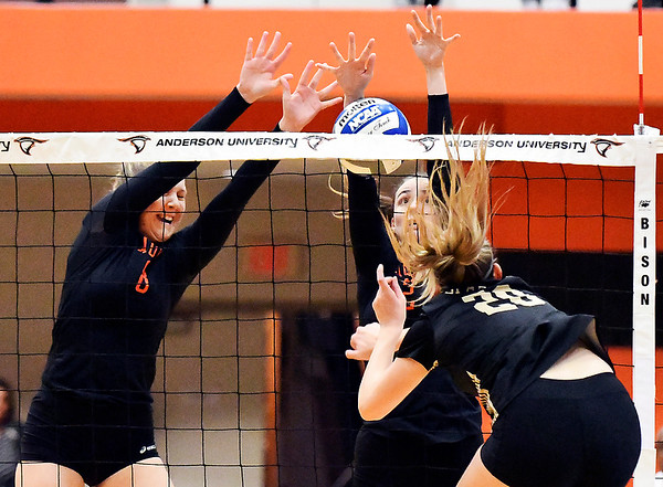 AU's Olivia Rice and Taylor Lawson try to block the ball on Manchester's Halle Planck's kill attempt.
