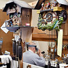 Joe Remington works at his bench in the background among the hanging clocks in the repair shop.
