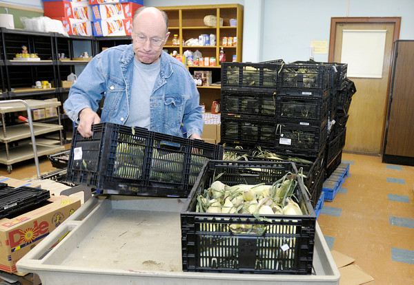 Volunteer Don Cruikshank loads a cart with sweat corn at Park Place Community Center Food Pantry on  Wednesday.