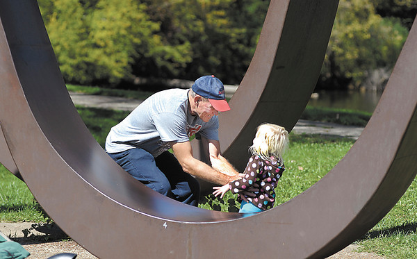 Zoy Lacy, 3, has fun keeping up with grandpa, Jerry Lacy of Alexandria, as they play games as they go around Shadyside Lake on a warm Monday afternoon.