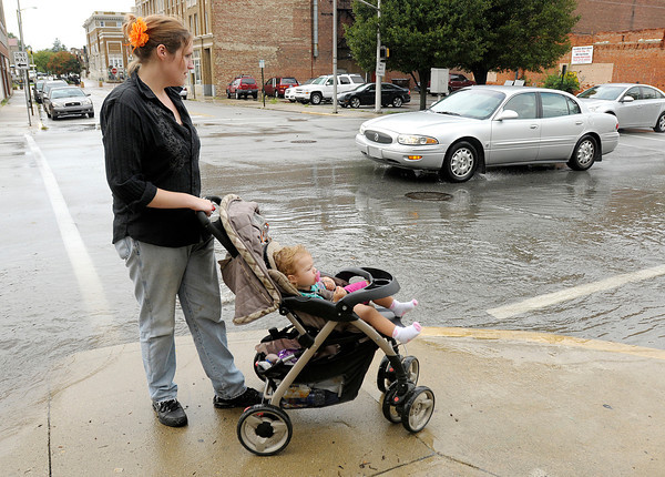 Barbie Fauss looks at flooding on main street with her daughter Emily after  thunderstorm dumped heavy rain Friday afternoon temporarily flooding some streets.
