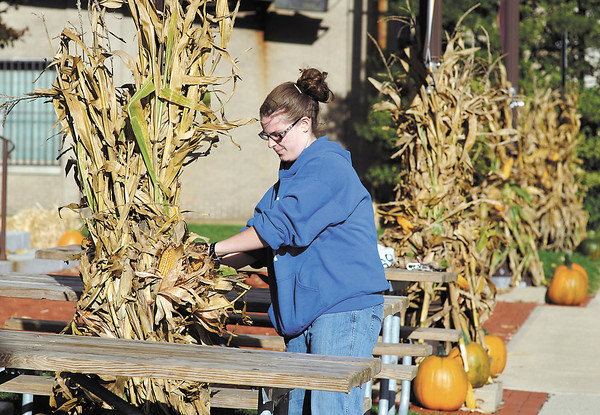 Myranda Beach, 8th grader from APA, decorates the lawn of the Anderson Center for the Arts Tuesday evening with some of her classmates for the Center's upcoming Octoberfest this Friday.