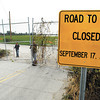 Anderson Municipal Airport employees Trent Saunders and Steve Darlington close and secure the large gates crossing Mounds Road out of Chesterfield Monday afternoon as that stretch of road that goes around the airport has now been permanently closed to traffic.