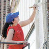 Brittney Wilhoit paints the front of the Christian Center on Wednesday. Volunteers from Lowe's spent two days sprucing up the center.