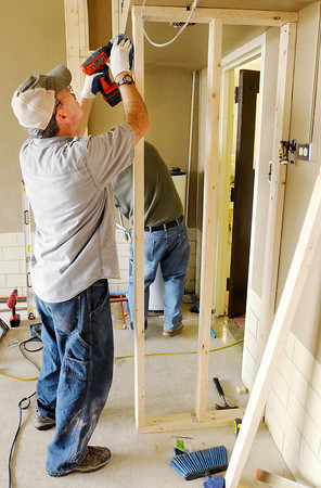 Dale Smith secures a wall stud as Faith Church volunteers remodel the kitchen at Mt. Pilgrim Church on Friday.