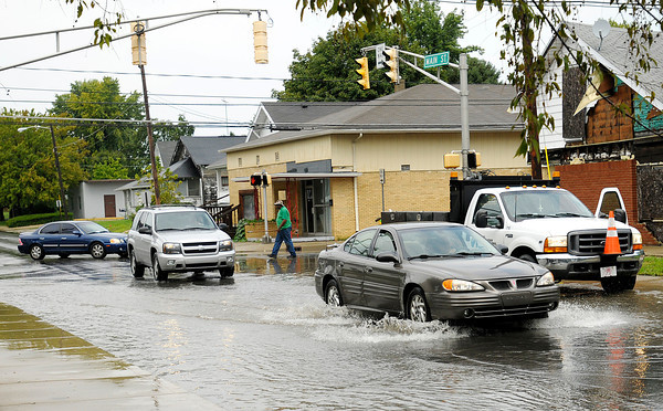Motorists navigate water on Main Street as an employee of Water Pollution Control checks the drains after a thunderstorm dumped heavy rain Friday afternoon temporarily flooding some streets.