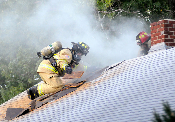 Anderson fire fighters open the roof of the home at 2308 Nichol Avenue while fighting a fire Wednesday evening.