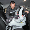 Chris Lamb checks to see that the child safety seat is properly installed in the back seat of the family car.
