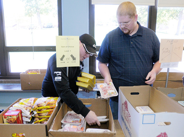 From left, Anderson University seminary students Rob Heaton and Rick Kohl restock a bin of frozen meat at the Park Place Community Center Food Pantry on  Wednesday.
