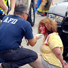This woman sits handcuffed on the ground in police custody while being checked out by Anderson Fire Department medical personnel after crashing her vehicle in the 1000 block of West Third Street in Anderson while being pursued by Madison County Sheriff's deputies Friday afternoon.