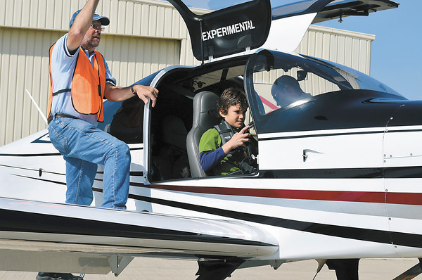 Michael Dixon, 10, puts on his headphones as Ron Waechter, Experimental Aircraft Accociation (EAA) member, closes the door on Jon Hubbel's award-winning airplane. The EAA took over 100 children for free rides at the Anderson Airport on Saturday