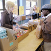 Anderson University seminary student Jenny Marble tells Frances Cooper the number of sandwiches she can have during food distribution at the Park Place Community Center Food Pantry on  Wednesday.