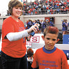 Elwood ball boy Julius Gerencser, 9, gets his hair painted red & blue by Kristina Retherford before the start of the game for homecoming.