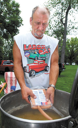 Tony Coppock puts more hotdogs into the cooker during the Madison County Solidarity Labor Day Picnic and Car Show Monday at Beulah Park in Alexandria. <br /> A steady crowd came out throughout the event as Coppock said he cooked up almost 3,000 hotdogs for the day.