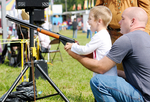 Ethan Turney, 4, reacts after shooting a balloon with a BB gun with a little help from his father Brock during Frankton Heritage Days on Saturday.