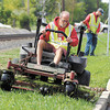 Greg Greenland cuts the grass in the right-of-way along east 32nd Street Friday as Jay Smith follows with a trimmer as city mowing crews work to keep up with the growing grass after all the rain.