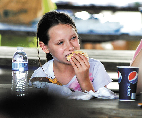 9 year old Grace Petty of Pendleton enjoys her hotdog with her family while at the Madison County Solidarity Labor Day Picnic and Car Show Monday.