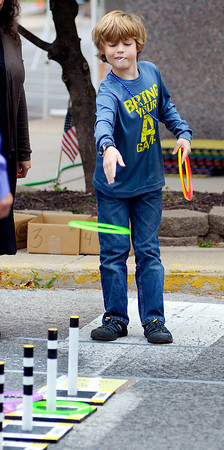 Harrison Binnion, 10, of Anderson, tries his luck at the ring toss game in the children's area at Octorberfest Friday in downtown Anderson.