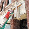 Don Stanley paints the front of the Christian Center on Wednesday. Volunteers from Lowe's spent two days sprucing up the center.