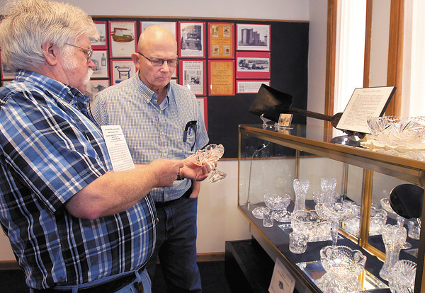 Madison County Historical Society volunteer Bill Knepp shows John Cunningham a piece from the collection of cut glass made by Thomas W. Wright of the Wright Rich Cut Glass company of Anderson.  This is part of the new glass exhibit at the Madison County Historical Society.