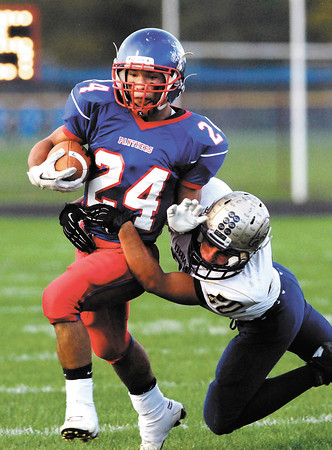 Elwood's Sammy Mireles runs out of the grasp of Oak Hill's Zack Daniels for another big gain.