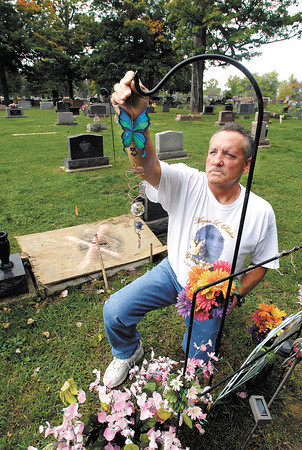 Rick Rider straitens Megan Rider's memorial at her grave site in Maplewood Cemetery Friday.  Megan was a victim of domestic violence.