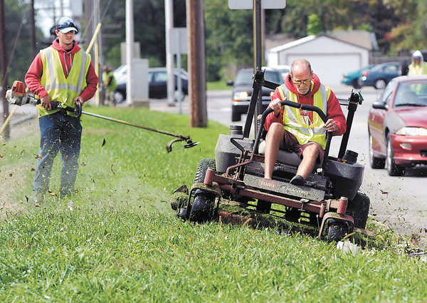 Greg Greenland cuts the grass in the right-of-way along east 32nd Street Friday as Jay Smith waits for him to pass to trim around the sign posts as city mowing crews work to keep up with the growing grass after all the rain.