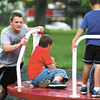 Michael Cook, 15, of Anderson, gives younger kids a push on the merry-go-round in the playground at Beulah Park Monday afternoon.