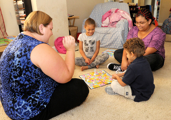 Hearther Foster plays a board game with her kids; Jamia, 7, Alexus, 14, and Cayleb, 4. Foster has received help from the St. Vincent de Paul Society.