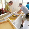 From left, Dillon Wilkins and Dave Aaron install cabinets as Faith Church volunteers remodel the kitchen at Mt. Pilgrim Church on Friday.