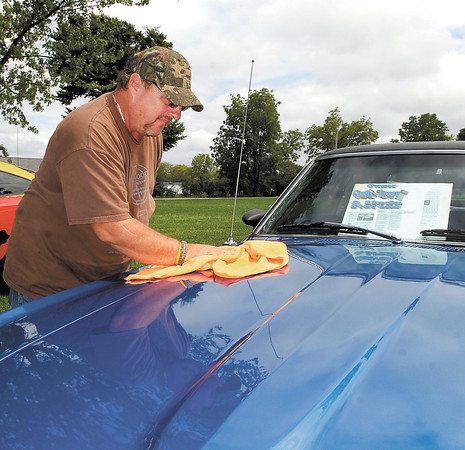 Rob Leathers of Anderson wipes down his 1969 Ford Mustang after a light rain shower passed over Beulah Park in Alexandria Monday afternoon at the Madison County Solidarity Labor Day Picnic and Car Show.