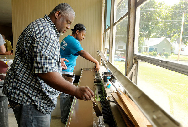 From left, Herb Johnson and Amber May paint as Faith Church volunteers remodel the kitchen at Mt. Pilgrim Church on Friday.
