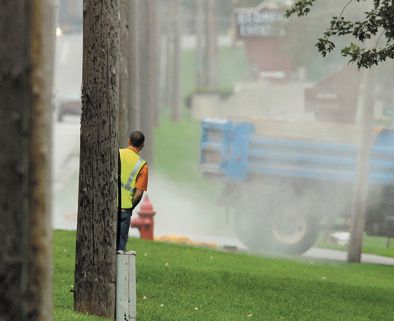 A city water department worker peers around the utility poles toward the gas leak that was filling the air after workers hit a 2-inch gas line near Red Bud Estates Friday morning.