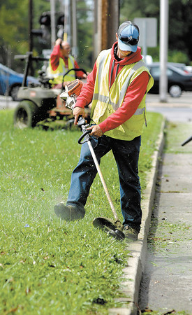 Jay Smith, of one of the city's mowing crews, trims along the curb along east 32nd Street as they mow and trim the right-of-way east of Columbus Ave. Friday afternoon.