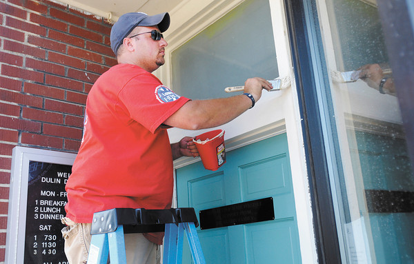 Chris Fetz paints the trim around a door at the Christian Center on Wednesday. Volunteers from Lowe's spent two days sprucing up the center.