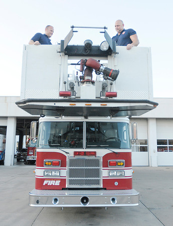 Don Knight/The Herald Bulletin<br /> From left, firefighters Kyle Amos and Joey Key stand on the platform of AFD's Ladder 1 truck on Thursday.