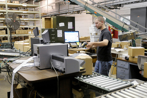 Don Knight/The Herald Bulletin<br /> Deven Renné prepares boxes for shipment at Warner Press on the campus of Anderson University.