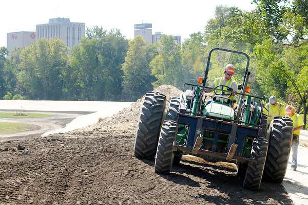 Don Knight/The Herald Bulletin<br /> A tractor is used to unfurl a matt to cover the soil of the new levee constructed at Athletic Park on Wednesday. The project is upgrading and extending the original levee built in the 30s.