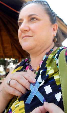 Kim Rogers-Hatfield, of United Way, pins on her ribbon in support of National Suicide Prevention Week at a informational rally Tuesday held at Citizens Plaza by the Madison County Suicide Prevention Coalition.