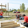 Don Knight/The Herald Bulletin<br /> Tracy Edwards assembles the framing for the roof of a bus shelter as employees from Lowes build a bus stop at Alternatives domestic violence shelter in Anderson on Tuesday. Working in the background from left are Eddie Edwards and Tim Turner.