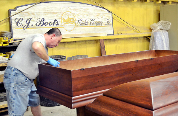 Dolphy Ryan hand rubs the stain on a casket at C.J. Boots Casket Company in downtown Anderson.