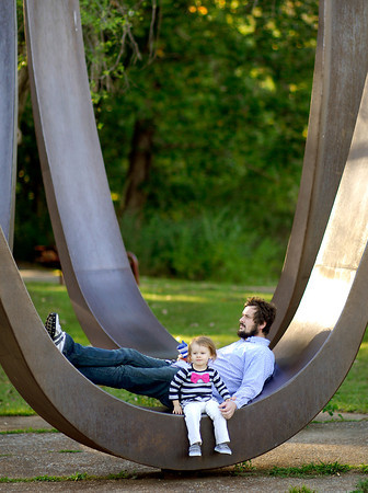 Josh Stafford takes a break with his daughter Sofia, 2, on one of the giant metal sculptures at Shadyside Lake Monday evening as they were enjoying an outing in the park.
