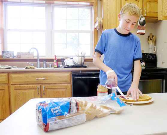 Don Knight/The Herald Bulletin<br /> Nathan Smith, 15, makes a peanut butter and jelly sandwich. Recognizing the problem of bread being squashed on the drive home from the store, Smith has invented a carrier to make sure bread makes it home from the grocery store in the same condition it was on the shelf.