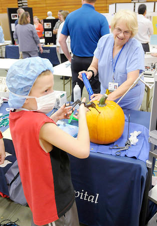 Don Knight/The Herald Bulletin<br /> St. Vincent's Kathy Jo Carter holds a flashlight up to a pumpkin as Skyler Ripperdan, 10, looks at a video monitor as he operates on the pumpkin during the Madison County Career Expo at Elwood High School and the John Hinds Career Center on Thursday.