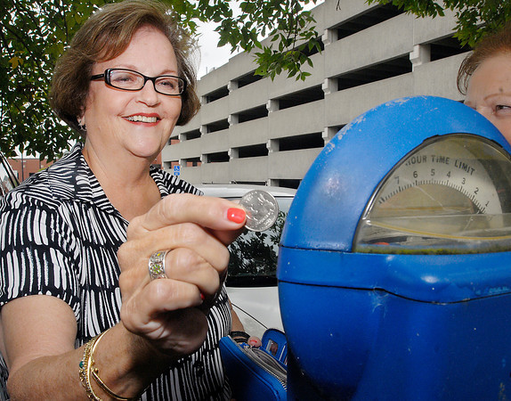 Merrellen Robinson, of Anderson, puts another quarter into the parking meter at the lot at 10th & Meridian Streets to make sure she would have sufficient time on the meter to enjoy lunch downtown Thursday with friends.